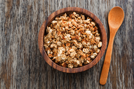 homemade granola in a wooden bowl and spoon, top view, close-up Standard-Bild