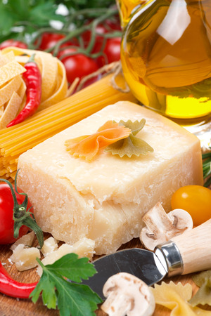 parmesan cheese, spices, tomatoes, olive oil, pasta and fresh herbs, close-up, vertical photo