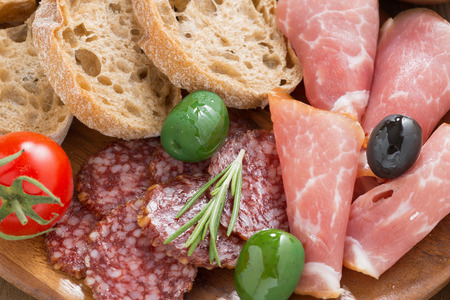 ciabatta: assorted Italian antipasti - deli meats, olives and bread, close-up, top view Stock Photo