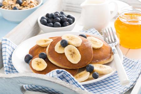 Pfannkuchen mit Banane, Honig und Blaubeeren zum Frühstück, horizontal