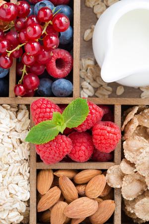 Alimentos para el desayuno - avena, granola, nueces, bayas y leche en caja de madera, vista desde arriba, vertical, primer plano Foto de archivo - 29811663