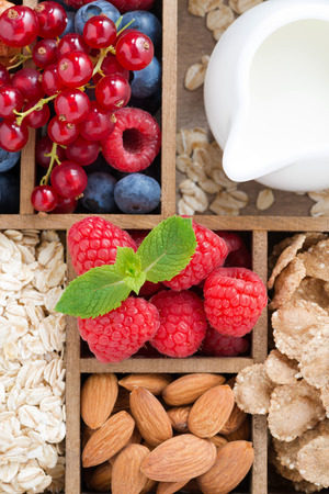 foods for breakfast - oatmeal, granola, nuts, berries and milk in wooden box, top view, vertical, close-up