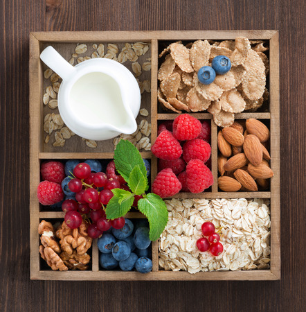 wooden box with breakfast items - oatmeal, granola, nuts, berries and milk, top view, close-up