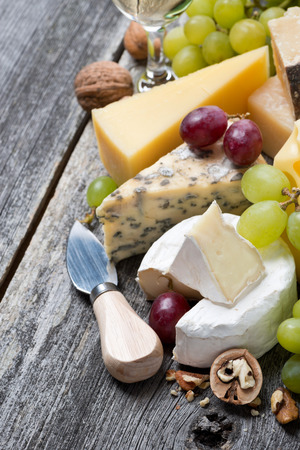 assortment of fresh cheeses, grapes and walnuts on a wooden background, top view, vertical photo
