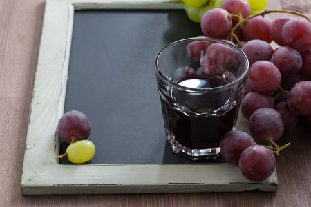 writing on glass: blackboard for writing, glass of red wine and grapes, horizontal