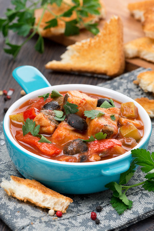 Fish stew with olives in tomato sauce, vertical, close-up photo