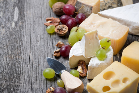 cheeses, grapes and walnuts on a wooden background, horizontal, close-up photo