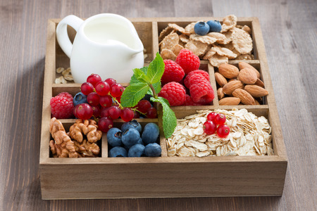 wooden box with breakfast items - oatmeal, granola, nuts, berries and milk on table