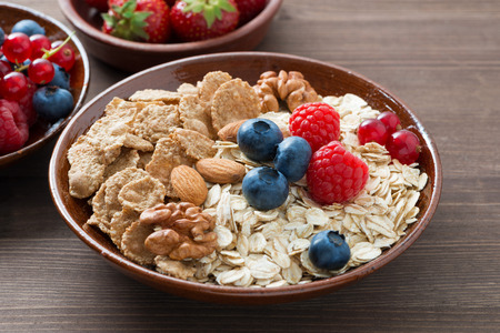 oatmeal and muesli in a bowl, fresh berries on wooden background, close-up, horizontal