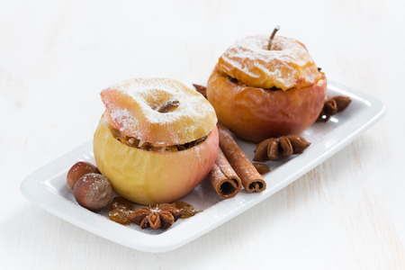 baked stuffed apples on a plate on white wooden table, horizontal, close-up photo