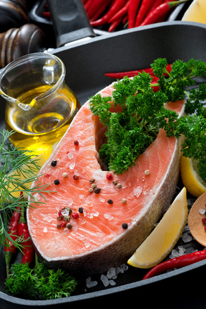 fresh salmon steak and ingredients for cooking on a grill pan, vertical, top view photo