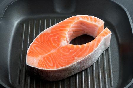 fresh salmon steak on the grill pan, top view photo