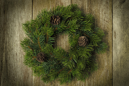 Christmas fir wreath on vintage wooden background, horizontal close-up photo