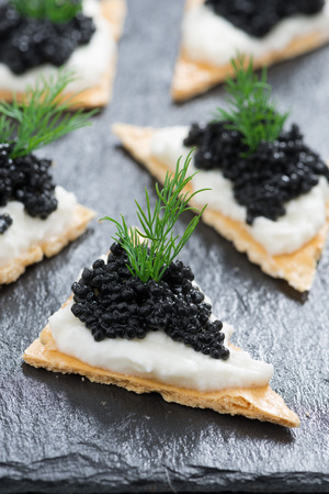 crackers with cream cheese and black caviar, vertical, close-up photo