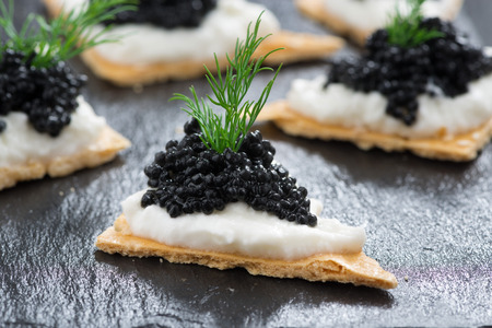 crackers with cream cheese and black caviar, horizontal photo