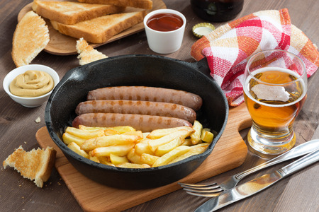 grilled sausages with French fries  in a frying pan, toasts and beer, top view photo