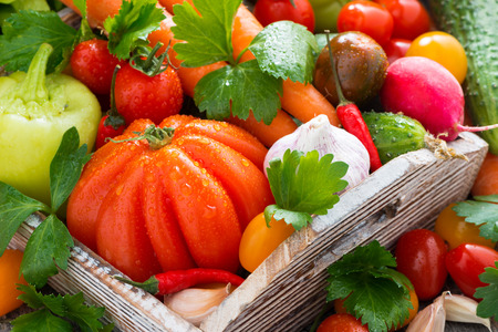 harvest of fresh seasonal vegetables in a wooden box, close-up, vertical photo