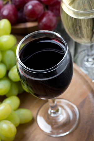 degustation: glasses of red and white wine and grapes, top view, close-up