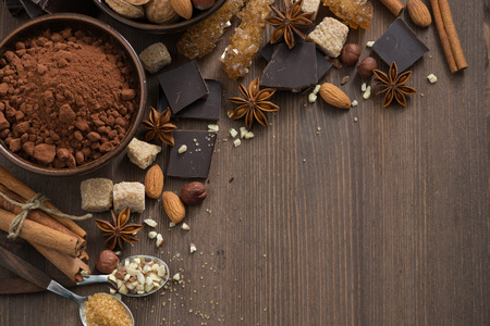 chocolate, cacao, frutos secos y especias sobre fondo de madera, vista desde arriba, horizontal