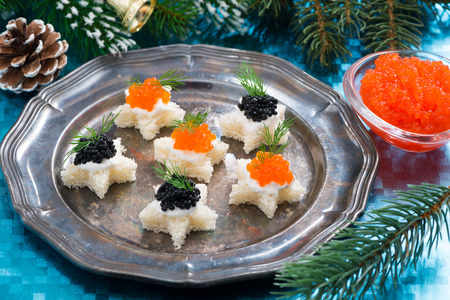 Christmas appetizers with caviar on a plate, close-up photo