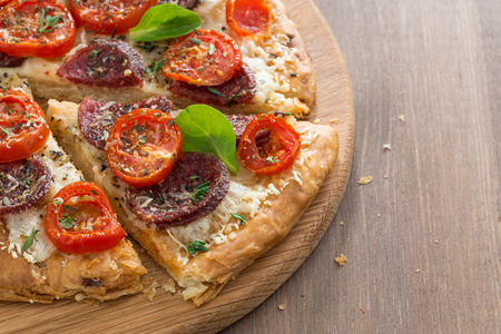delicious pizza with salami and tomatoes on a wooden background, top view, close-up photo