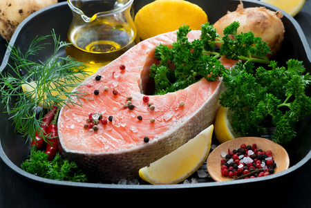 raw salmon steak and ingredients for cooking on a grill pan, horizontal photo