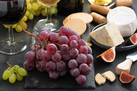 bunch of red grapes, assorted cheeses and appetizers on dark background, close-up photo