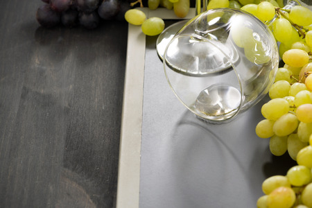 empty wine glass and grapes on a blackboard, horizontal, close-up photo