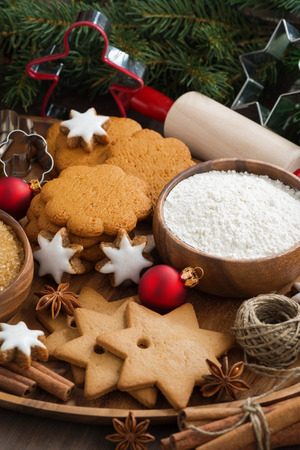 Assorted Christmas cookies and ingredients for baking, vertical, top view photo