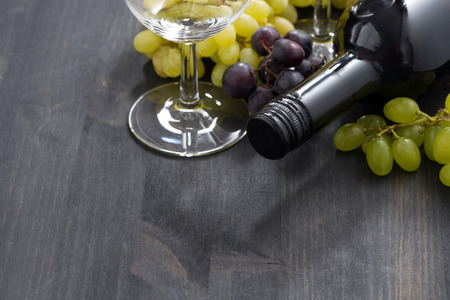 bottle of red wine, empty glass and grapes on a dark wooden background, horizontal photo