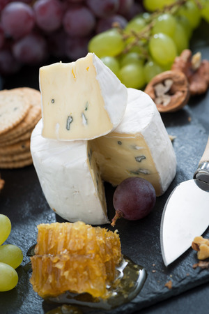Camembert with fresh honey, grapes and nuts, close-up, vertical photo