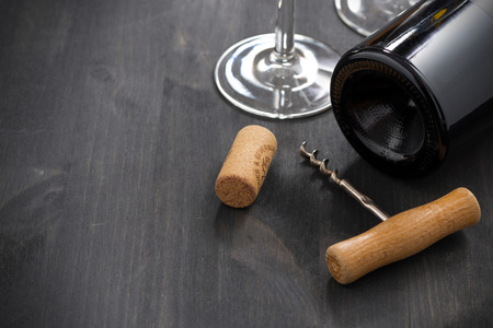 bottle of red wine, corkscrew and empty glass on a wooden background, close-up photo