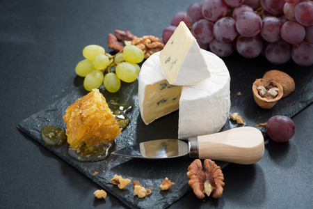Camembert with fresh honey, grapes and nuts on dark background, horizontal, close-up photo