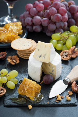 Camembert with fresh honey, grapes and nuts, vertical, top view photo