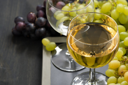 glass of white wine and assorted grapes on a blackboard, close-up photo