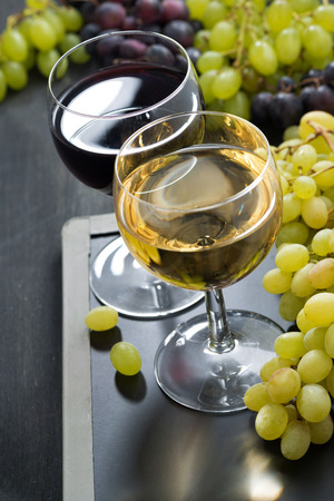 glasses of white and red wine and grapes on a blackboard, close-up photo