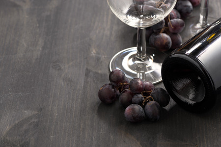 bottle of red wine, glasses and grapes on a wooden background, horizontal photo