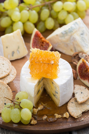 camembert with honey and fruit, snacks on a wooden tray, vertical, close-up photo