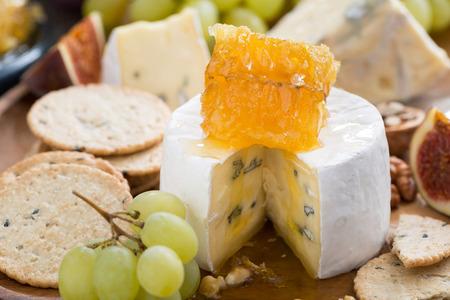 camembert with honey and fruit, snacks, close-up, horizontal photo