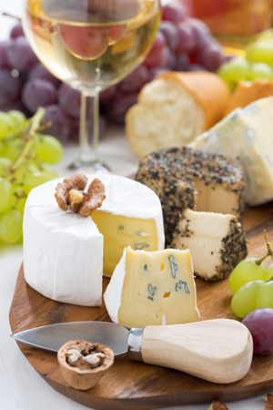 cheese platter, snacks, bread and wine on wooden board, vertical, close-up photo