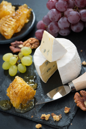 delicious Camembert with fresh honey, grapes and nuts on a dark background, top view, vertical photo