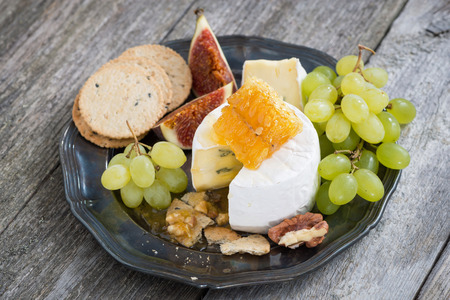 fresh camembert with honey, grapes and crackers on a plate, top view, horizontal photo