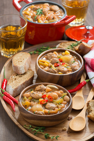 vegetable stew with sausages in a wooden bowl, vertical, top view, close-up photo