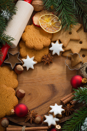 wooden background with Christmas cookies and ingredients for baking, vertical, top view photo