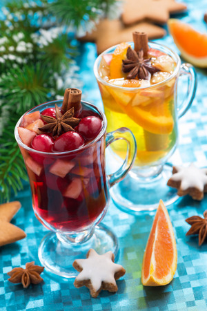 Christmas mulled wine and spiced apple cider on a blue background, vertical, close-up photo