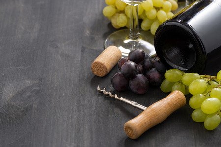 bottle of red wine and grapes on a wooden background photo