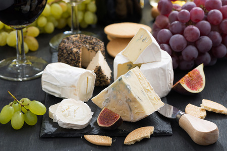 delicacy soft cheeses, fruit and crackers, close-up Standard-Bild