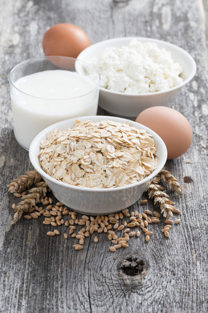 fresh products - oatmeal, eggs, cottage cheese and milk on wooden background, vertical photo