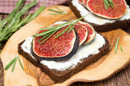 rye bread with goat cheese, fresh figs, honey and rosemary, close-up photo