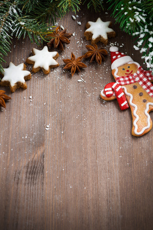 dark wooden background with fir branches, cookies and gingerbread man, vertical, top view photo